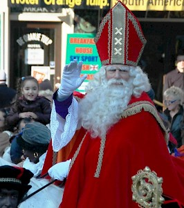 Sinterklaas arrives in Amsterdam; note that there is no Christian cross on his mitre, but Amsterdam's weapon