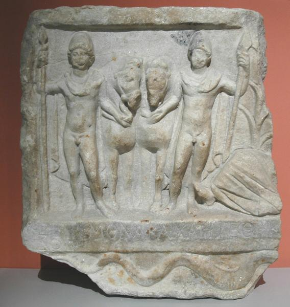 A relief showing the Dioscuri and the river god (to the right; only his legs are visible)
