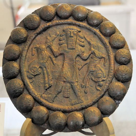 Disk with a deity with a mythological scene